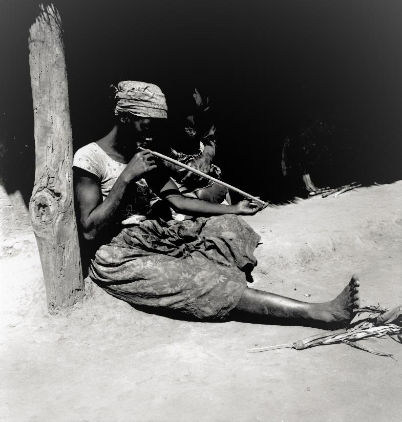 FIGURE 5(a). Ryness Gondwe playing the mtyangala mouth-resonated musical stick made from reed (bot. Phragmites mauritanus)