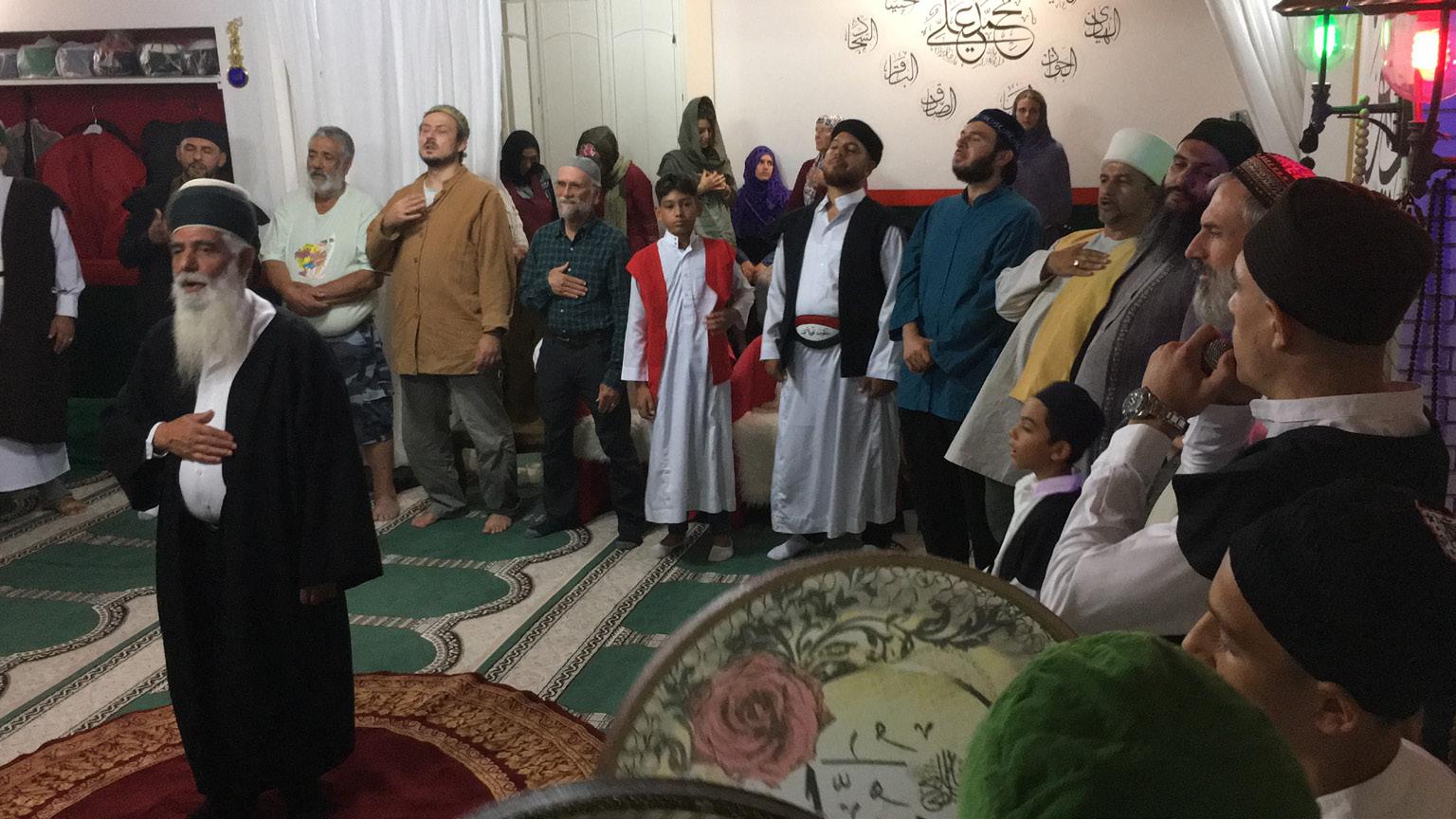 FIGURA 6. Baba Dzevat al centro della halka percorre il perimetro del cerchio in senso antiorario elargendo benedizioni a tutti i presenti (ʿĀšūrāʾ, 14 settembre 2019, frame da video di M. R. Coppola).