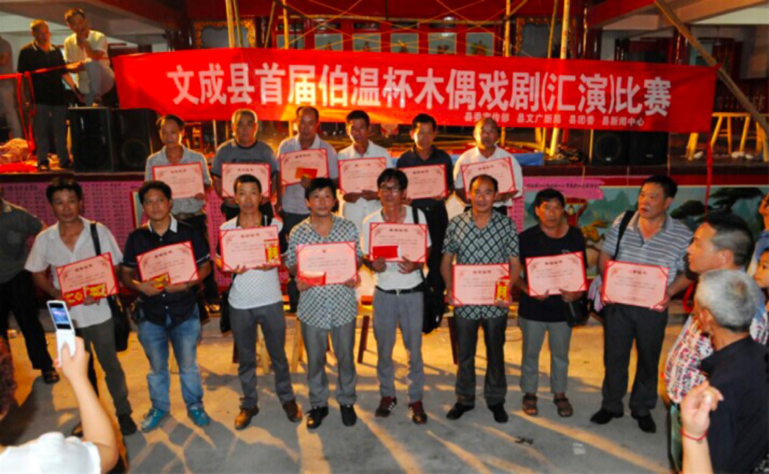 """FIGURA 2. Primo festival delle marionette di Wencheng, anno 2014. Il quinto da destra della prima fila è Huan Bingkuan, il marionettista della """"Compagnia di Marionette del Drago di Wencheng"""" (foto concessa da H. Bingkuan)."""