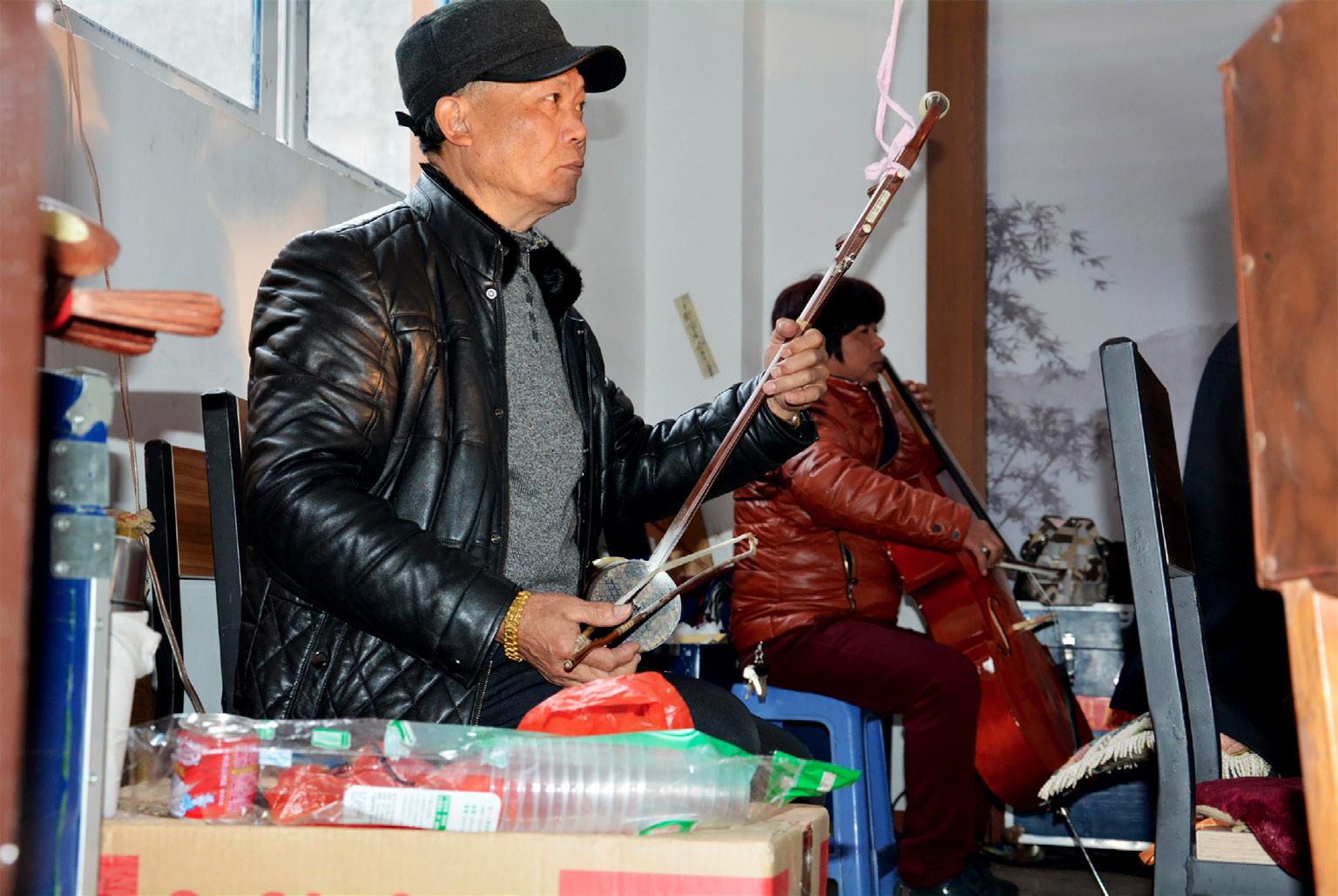 FIGURA 7. Erhu e violoncello durante uno spettacolo di marionette a Wencheng. In primo piano con l'erhu Yong Zhong, presidente dell'associazione per la musica etnica di Wencheng (foto: F. Serratore).