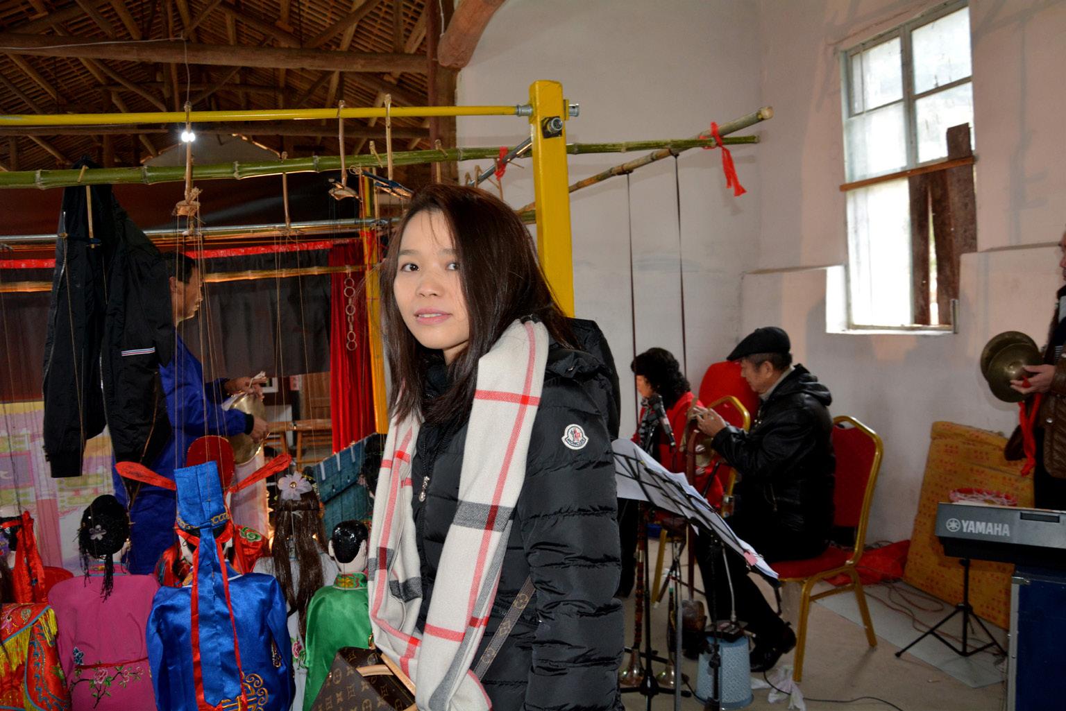 FIGURA 9. Fan Fan, barista cinese della provincia di Milano mentre osserva il backstage dello spettacolo di marionette a Fu'ao (foto: F. Serratore).
